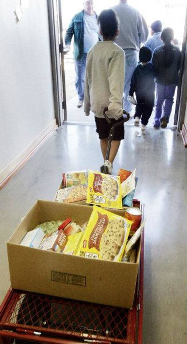 A child helps load food from the Angel Food Ministries in this photo taken in November 2006 at Trinity Lutheran Church in Oklahoma City.  <strong>Jaconna Aguirre - The Oklahoman, Archive Photo</strong>