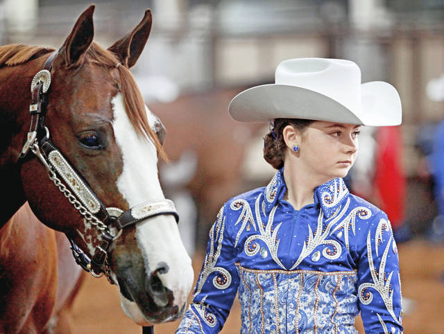 Bailey Cook, 11, of California, stands next to Ima Gallant Titan, 11, on Saturday during the Oklahoma Holiday Classic paint horse show at State Fair Park in Oklahoma City. Photo by Bryan Terry, The Oklahoman