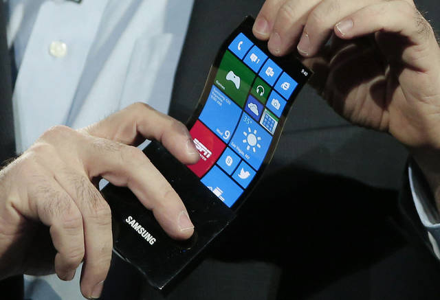 Eric Rudder, chief technical strategy officer of Microsoft, holds a prototype Windows smartphone with a flexible OLED display Wednesday during Samsung�s keynote address at the consumer electronics show in Las Vegas. AP Photo