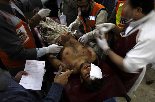 Pakistani volunteers rush an injured person to an emergency ward at a local hospital in Peshawar, Pakistan on Friday, Feb. 1, 2013. A suicide bomber detonated his explosives outside a Shiite mosque in northwestern Pakistan as worshippers were leaving Friday prayers, killing several people and wounding dozens in the latest apparent sectarian attack in the country, police said.(AP Photo/Mohammad Sajjad)