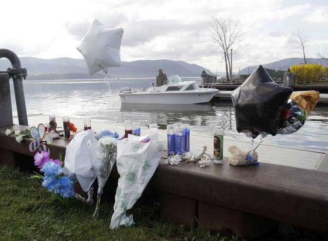 A fisherman is seen behind an informal memorial at the boat ramp where Lashanda Armstrong drove her minivan into the Hudson River on Tuesday night killing herself and three of her children, in Newburgh, N.Y., on Thursday, April 14, 2011. (AP Photo/Mike Groll)