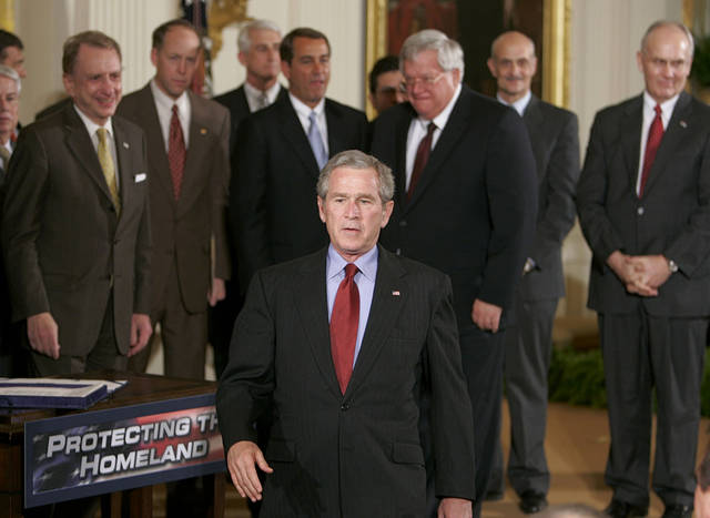 "FILE - In this March 9, 2006 file photo, members of Congress watch as President George W. Bush leaves the stage after signing the USA Patriot Terrorism Prevention Reauthorization Act, in the East Room of the White House in Washington. We are safer, but not safe enough. In the decade since the 9/11 attacks, the government has taken giant steps to protect the nation from terrorists, spending eye-popping sums to smarten up the federal bureaucracy, hunt down enemies, strengthen airline security, secure U.S. borders, reshape America's image and more. But the effort remains a work in progress, and in some cases a work stalled. The bipartisan 9/11 Commission in 2004 laid out a 585-page road map to create an America that is ""safer, stronger, wiser."" Many of the commission's recommendations are now reality. But in some cases, results haven't lived up to expectations. And other proposals still are just that, ideas awaiting action. (AP Photo/Ron Edmonds, File)"
