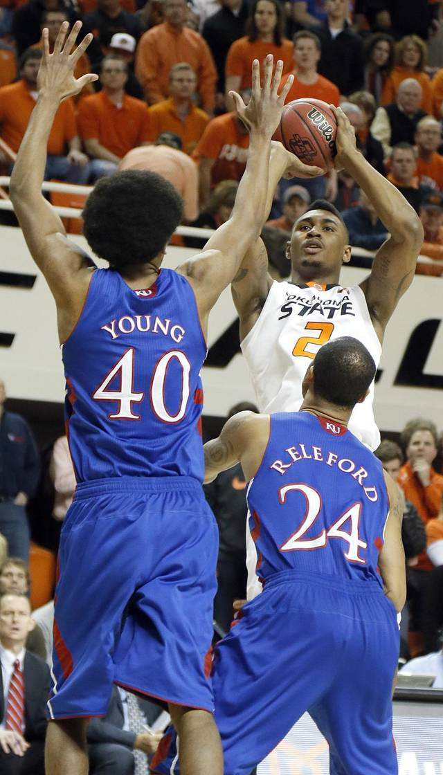 Oklahoma State 's Le'Bryan Nash (2) shoots over Kansas' Kevin Young (40) and Travis Releford (24) during the college basketball game between the Oklahoma State University Cowboys (OSU) and the University of Kanas Jayhawks (KU) at Gallagher-Iba Arena on Wednesday, Feb. 20, 2013, in Stillwater, Okla. Photo by Chris Landsberger, The Oklahoman