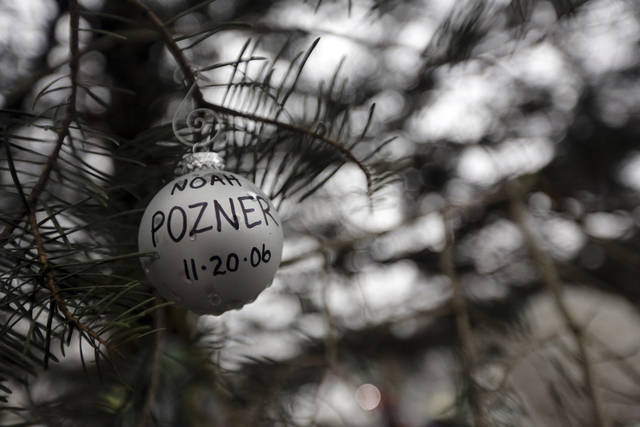 An ornament for Noah Pozner hangs on a tree at one of the makeshift memorials for the Sandy Hook Elementary School shooting, Monday, Dec. 17, 2012 in Newtown, Conn. Pozner was killed when a gunman walked into Sandy Hook Elementary School in Newtown Friday and opened fire, killing 26 people, including 20 children. (AP Photo/Mary Altaffer) ORG XMIT: CTMA105