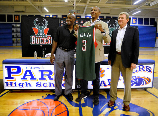 Milwaukee Bucks' Caron Butler holds up a jersey as he stands with Bucks coach Larry Drew, left, and general manager John Hammond, during a news conference the NBA basketball team held before students in the Park High School gymnasium on Thursday, Sept. 5, 2013, in Racine, Wis. Butler is from Racine and is a Park High School alumnus. (AP Photo/The Journal Times, Scott Anderson)