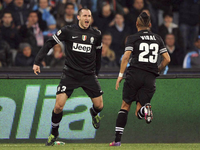 Juventus' Giorgio Chiellini, left, celebrates with Chilean teammate Arturo Vidal after scoring during an Serie A soccer match between Napoli and Juventus, at the San Paolo stadium in Naples, Italy, Friday, March 1, 2013. (AP Photo/Francesco Pecoraro) ITALY OUT