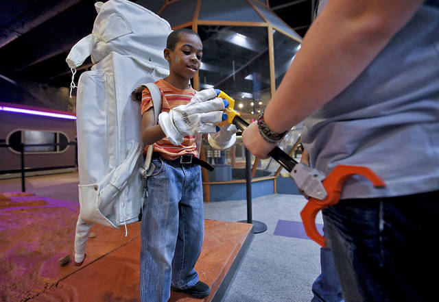 Michael Smith puts on part of a NASA space suit at Science Museum Oklahoma as he learns what it is like to collect rocks on Mars. The museum offered space experiments as the Space Shuttle Discovery was transported to the Smithsonian's National Air and Space Museum. PHOTOS BY CHRIS LANDSBERGER, THE OKLAHOMAN