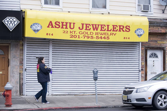 An FBI agent walks past Ashu Jewelers at 814 Newark Ave. in Jersey City on Tuesday, Feb. 5, 2013, one of the stores allegedly involved in an international credit card fraud ring. Eighteen people were charged in what may be one of the nation's largest credit card fraud rings, a sprawling international scam that duped credit-rating agencies and used thousands of fake identities to steal at least $200 million, federal authorities said Tuesday. (AP Photo/The Jersey Journal, Reena Rose Sibayan)