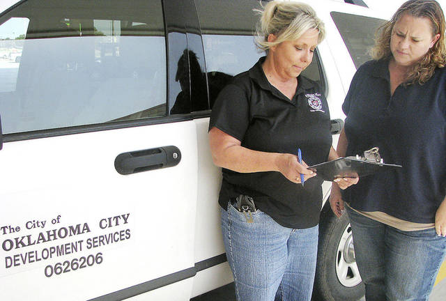 Code enforcement officer Tammie Brimm looks over a sheet of complaints with trainee Theresa Samples in July in Oklahoma City. Photo by Vallery Brown, The Oklahoman