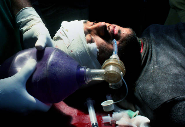 A Pakistani injured polio worker is treated at a local hospital in Peshawar, Pakistan on Wednesday, Dec. 19, 2012. Gunmen shot dead a woman working on U.N.-backed polio vaccination efforts and her driver in northwestern Pakistan, officials said, just a day after similar attacks across the country killed several female polio workers. (AP Photo/Mohammad Sajjad)