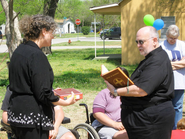 Jana Castleberry, Cleveland County Habitat for Humanity executive director, holds a family Bible as the Rev. Edward Menasco, pastor of St. Joseph Catholic Church, blesses it for the Baker family.
