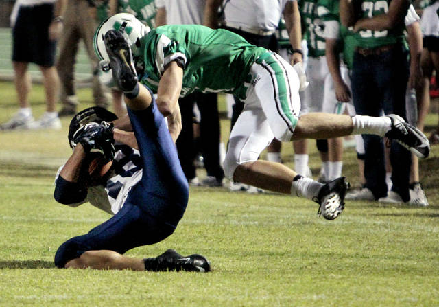El Reno's Seth Jones catches a pass and is tackled by McGuinness' Cody Chancellor as the Indians play the Bishop McGuinness Fighting Irish in high school football on Friday, Sept. 21, 2012 in Oklahoma City, Okla.  Photo by Steve Sisney, The Oklahoman