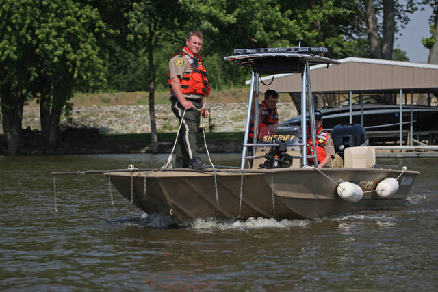 Des Moines County officer Kevin Glendening, foreground, drags the Mississippi River as officer Brad Siegfried, center, and Sheriff Mike Johnstone use sonar to locate four missing people near O'Connel Slough Saturday, May 19, 2012 near Burlington, Iowa. Two boats collided early Saturday morning leaving eight injured and four missing. (AP Photo/The Hawk Eye, Brenna Norman)