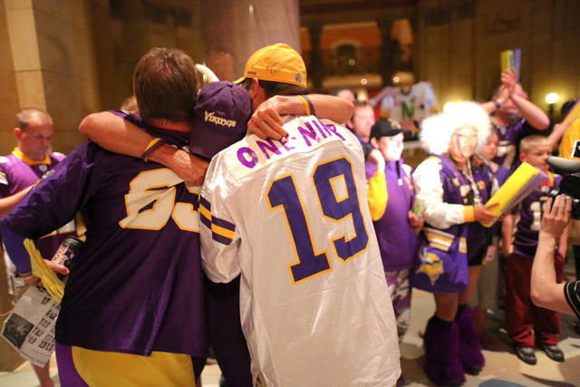 Tom Nickerson, Larry Spooner and Diggz Garza embraced after the debate on the stadium bill passed in the House Monday night, May 7, 2012 at the Capitol in St. Paul, Minn. The Minnesota House has approved a plan to build a $975 million stadium for the Vikings, but with a big boost in what the team would pay. (RENEE JONES SCHNEIDER * reneejones@startribune.com)(AP Photo/The Star Tribune, Renee Jones Schneider ) MANDATORY CREDIT; ST. PAUL PIONEER PRESS OUT; MAGS OUT; TWIN CITIES TV OUT