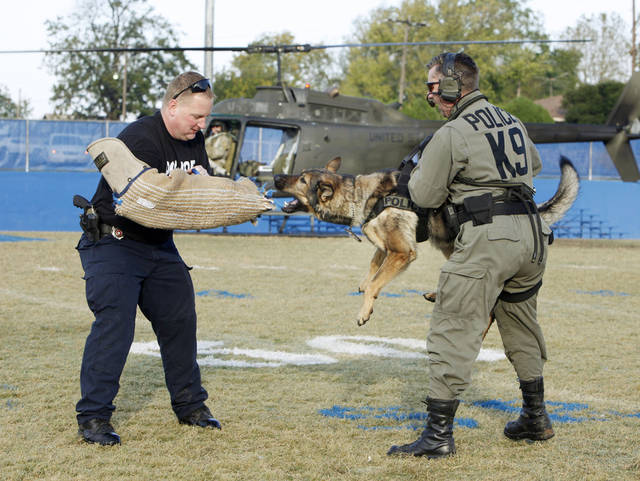 "Harrah Police Officer Phil Stewart holds police dog ""Ajo"" as he bites the protected arm of Officer John Williams during a demonstration at Harrah High School in Harrah, OK, Friday, Oct. 28, 2011. Members of the Harrah Police Department and various federal agents spoke to students about aspects of their jobs and the need to stay away from illegal drugs. The demonstrations were a part of Red Ribbon Week at the school. By Paul Hellstern, The Oklahoman"