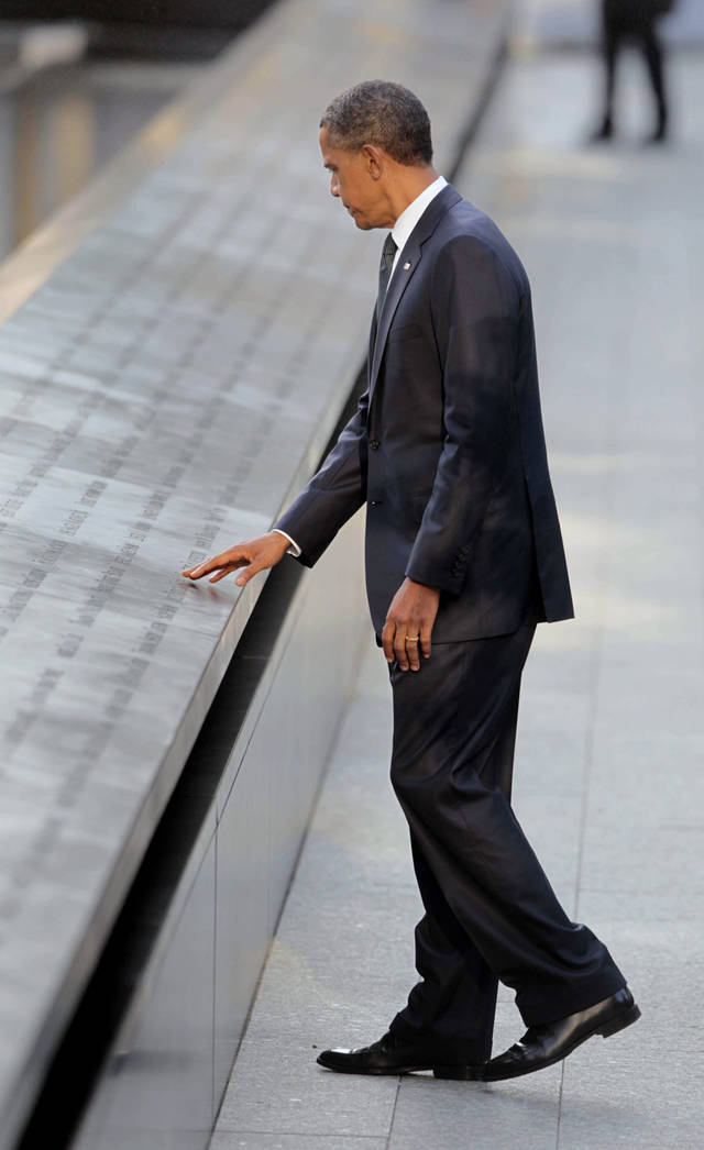   President Barack Obama touches names of the 9/11 victims as he visits the North Memorial Pond at the National Sept. 11th Memorial ceremony Sunday, Sept., 11, 2011 in New York. (AP Photo/Pablo Martinez Monsivais)  