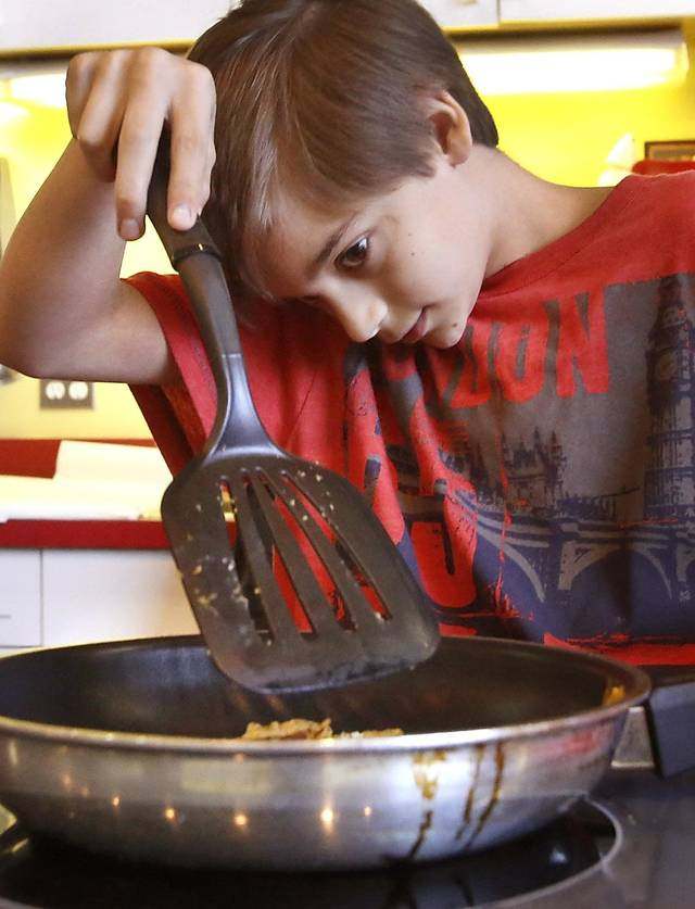 Zachary Jenkins, 11, checks to see if his  pumpkin spice pancake is cooked enough to flip while competing in the Shawnee Mills&#039;  Kids&#039; Pancakes, Flapjacks and Griddle Cakes Contest at the Oklahoma State Fair on Saturday, Sep. 22, 2012. The event was held in the Creative Arts Building. Jenkins lives in Newalla and is a 6th grade home-schooled student.   Photo by Jim Beckel, The Oklahoman.