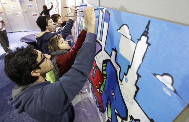 Jay Desai, of Washington, front and Ariel Timar, of Cherry Hill, N.J., center, paint a mural as they participate in the National Day of Service on the Mall as part of the 57th Presidential Inaugural festivities, Saturday, Jan. 19, 2013, in Washington, . The two were working on the Greater DC care project that will place the murals in schools and fire stations to help promote volunteerism.   (AP Photo/Steve Helber)