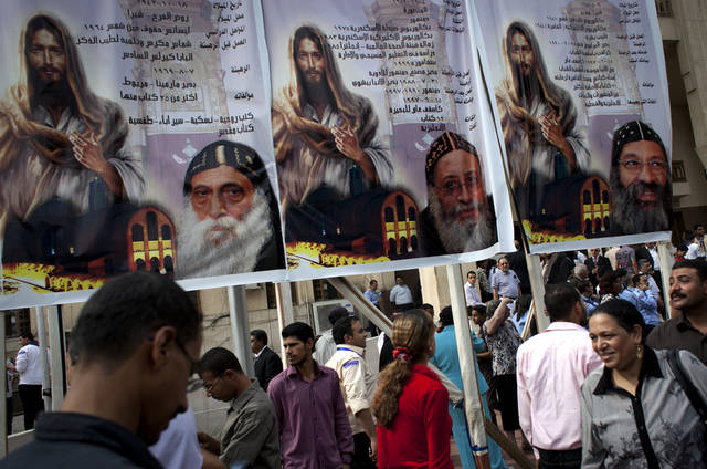 Egyptian Copts walk past an election poster with pictures of the three candidates, Father Raphael Ava Mina, left, Anba Tawadros, center and Anba Raphael, right following the papal election ceremony at the Coptic Cathedral in Cairo, Egypt, Sunday, Nov. 4, 2012. Egypt's ancient Coptic Christian church named a new pope on Sunday, Nov. 4, 2012 to spiritually guide the community through a time when many fear for their future with the rise of Islamists to power and deterioration in police powers after last year's uprising. (AP Photo/Nasser Nasser)