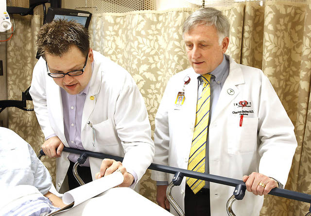 Registered nurse Michael Swift, left, and Dr. Charles Bethea go over a consent form that was individualized to a patient using an electronic database.photo by PAUL B. SOUTHERLAND, the oklahoman