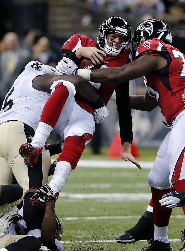 Atlanta Falcons quarterback Matt Ryan, center, is sacked by New Orleans Saints defensive end Tyrunn Walker, left, in the first half of an NFL football game in New Orleans, Sunday, Sept. 8, 2013. (AP Photo/Bill Haber)