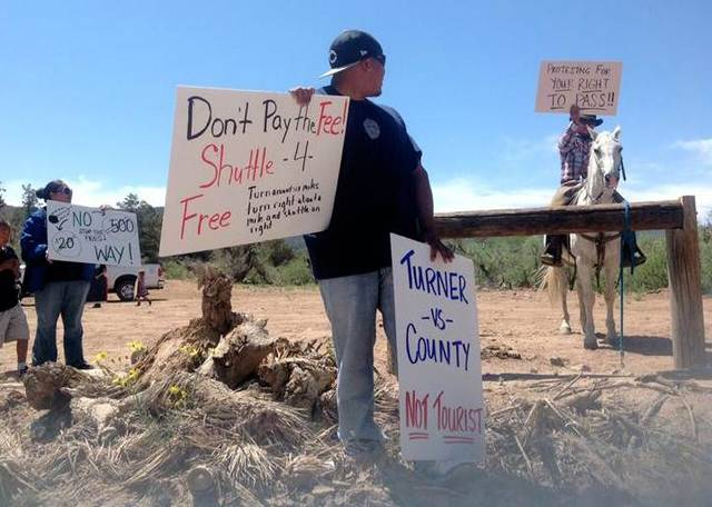 In this Tuesday, May 28, 2013 photo provided by the Hualapai tribe, members of the Hualapai tribe protest as a private armed guard collects tolls of $20.00 per person and up to $500.00 per tour bus on the Diamond Bar Road checkpoint leading to the Grand Cayon Skywalk in Meadview, Nev. Land owner Nigel Turner recently set up a checkpoint and started charging tourists driving through his ranch to get to the Grand Canyon Skywalk, which he calls an admission fee. While the fee includes access to an hourly rodeo show and other ranch activities, the Hualapai Indian tribe - which operates the Skywalk - says the fee is unethical and potentially illegal. (AP Photo/Hualapai Tribe, Dave Cieslak)