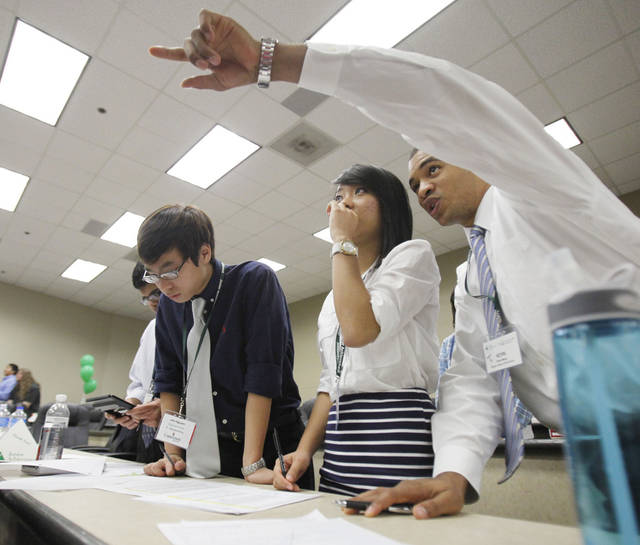 John Nguyen (left), Mai Vu, and Kevin More watch the direction of stocks as they play the  Investor Challenge game at Southern Nazarene University in Bethany, OK, Thursday, Oct. 6, 2011. By Paul Hellstern, The Oklahoman