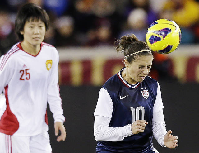 United States' Carli Lloyd (10) heads the ball in front of China's Zhang Rui during the first half of an exhibition soccer match, Wednesday, Dec. 12, 2012, in Houston. (AP Photo/David J. Phillip)