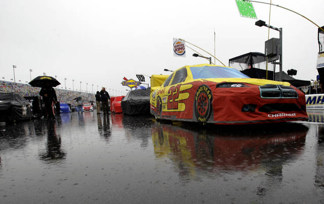 AJ Allmendinger's car (22) and others remain parked on pit road due to a rain delay before the start of the Daytona 500 auto race at Daytona International Speedway in Daytona Beach, Fla., Sunday, Feb. 26, 2012. (AP Photo/John Raoux)