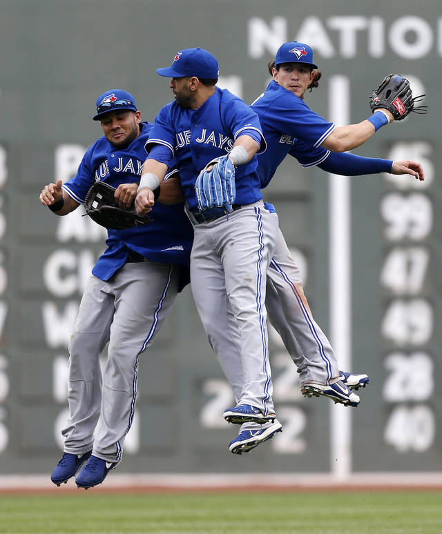 Toronto Blue Jays', from left, Melky Cabrera, Jose Bautista and Colby Rasmus celebrate after defeating the Boston Red Sox 3-2 in a baseball game in Boston, Saturday, May 11, 2013. (AP Photo/Michael Dwyer)