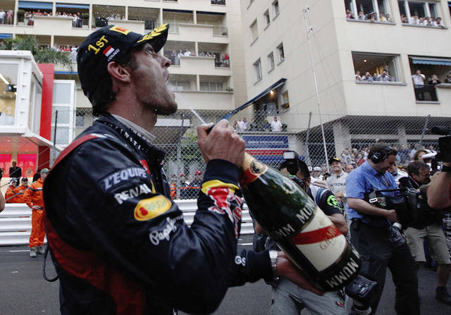 Red Bull driver Mark Webber of Australia celebrates with champagne after winning the Formula One Grand Prix, at the Monaco racetrack, in Monaco, Sunday, May 27, 2012. (AP Photo/Luca Bruno)