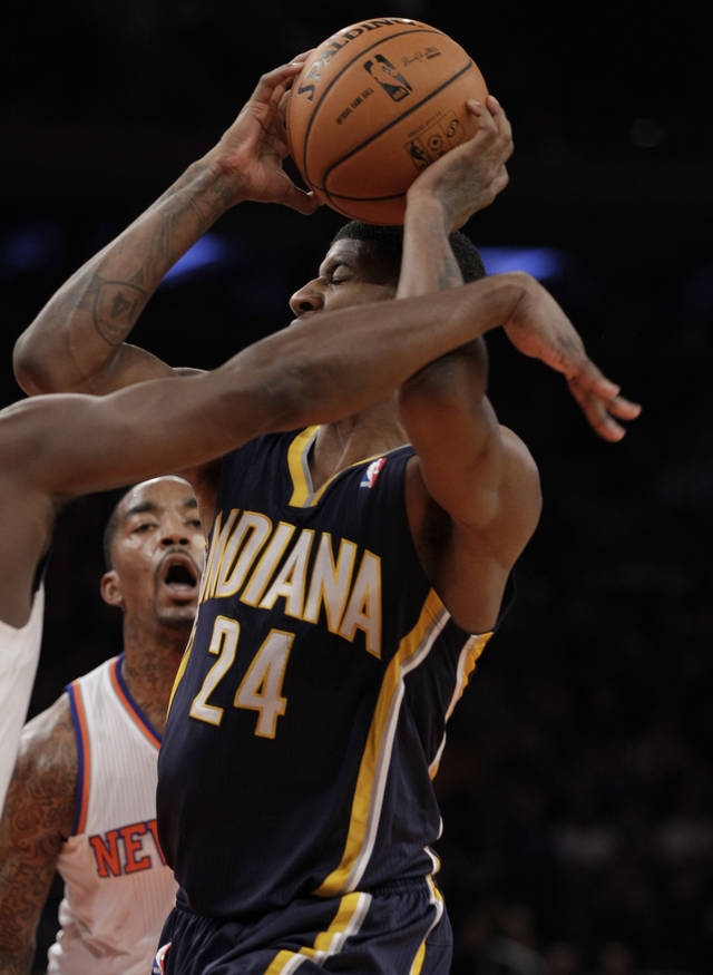 Indiana Pacers forward Paul George dodges the New York Knicks defense as Knicks guard J.R. Smith looks on in the first half of their NBA basketball game at Madison Square Garden in New York, Sunday, Nov. 18, 2012. (AP Photo/Kathy Willens)