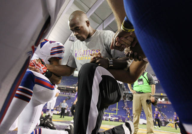 Minnesota Vikings running back Adrian Peterson (28) prays with players from both the Vikings and the Buffalo Bills after an NFL preseason football game, Friday, Aug. 17, 2012, in Minneapolis. The Vikings won 36-14. (AP Photo/Genevieve Ross)
