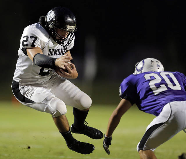 Perkins' Tyler Taff rushes as Bethany's Brady Van Zant looks to make a tackle during the high school football game between Bethany High School and Perkins in Bethany, Okla., Friday, Sept. 28, 2012.  Photo by Sarah Phipps, The Oklahoman