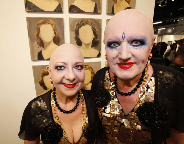 German performance artists Eva & Adele pose for a photo in front of an untitled work by Gideon Rubin during a VIP and media preview of Art Basel Miami Beach, Wednesday, Dec. 5, 2012 in Miami Beach, Fla. Art Basel Miami Beach and about two dozen other independent art fairs open Thursday. Tens of thousands of people are expected through Sunday at the fairs throughout Miami and South Beach. (AP Photo/Wilfredo Lee)