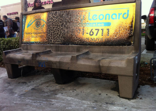 A burned city bus bench seen in the Van Nuys section of Los Angeles on Thursday Dec. 27,2012 after police arrested a man for allegedly setting a 67-year-old woman on fire who was sleeping on the bus stop bench. Authorities said the man, who is in his 20s, was arrested early Thursday. Police said the attack occurred shortly after 1 a.m. outside a drug store. A witness said he saw a man come out of the store and pour something on the woman who had been sleeping on a bench before striking a match and setting her ablaze. The woman, who may be homeless, was taken to a hospital and listed in critical condition. (AP Photo/Greg Risling)