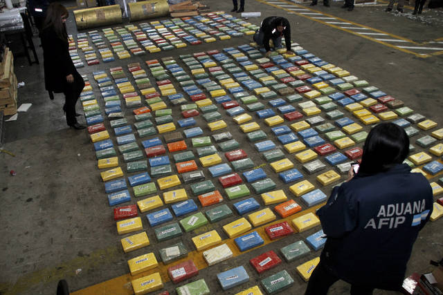In this picture released by Argentina's Customs, customs officers count packages containing 536 kilograms (1,181 pounds) of cocaine they found hidden inside a machine to be exported to Nigeria Friday, July 20, 2012, in Buenos Aires, Argentina. (AP Photo/Argentina's Customs)