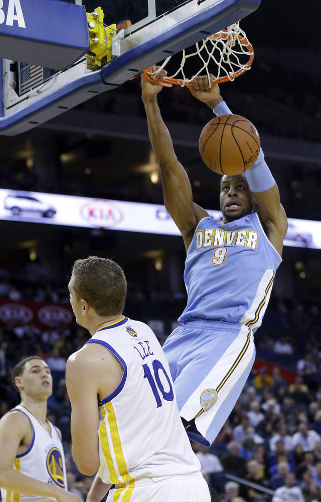 Denver Nuggets' Andre Iguodala (9) dunks over Golden State Warriors' David Lee (10) during the first half of an NBA basketball game in Oakland, Calif., Thursday, Nov. 29, 2012. (AP Photo/Marcio Jose Sanchez)