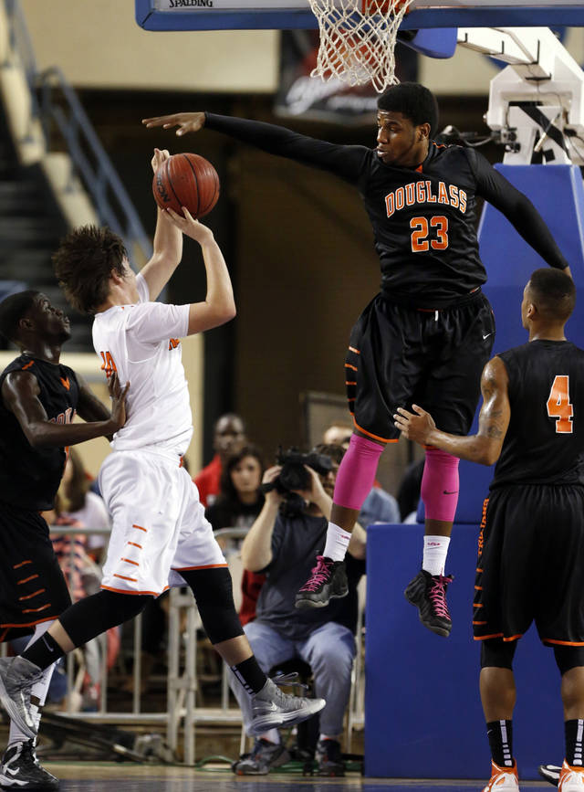 Douglass' Deondre Clark blocks a shot by Gunner Lynch during the 4a boys championship game where the Douglass high school Trojans play the Roland Rangers at the State Fair Arena on Saturday, March 9, 2013 in Oklahoma City, Okla.  Photo by Steve Sisney, The Oklahoman