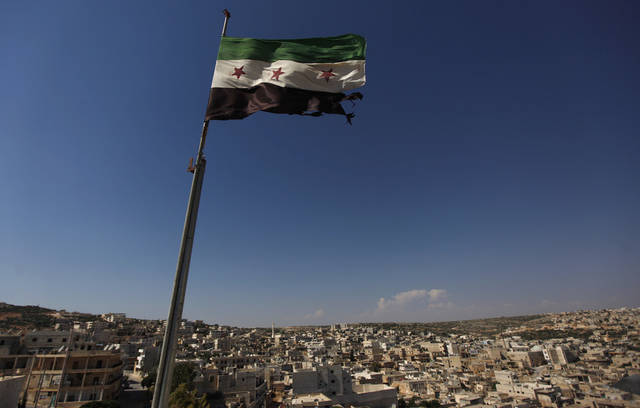 FILE - This June 12, 2012 file photo shows a Syrian revolutionary flag waving on top of a building on the outskirts of Aleppo, Syria. Syria's conflict is the most violent to emerge from last year's Arab Spring. The protests started peacefully but prompted a brutal crackdown by President Bashar Assad's government. The fighting has escalated into a civil war that has killed just over 30,000 people over the last year and a half, according to activists. Despite intervening in Libya, the United States has steered clear of taking military action or arming Syria's rebels. (AP Photo/Khalil Hamra, File)