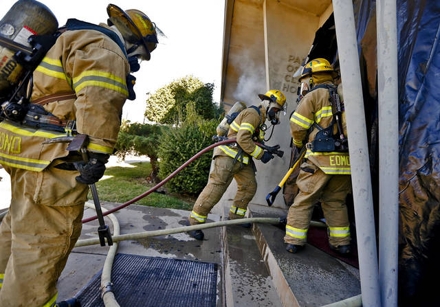 Edmond firefighters prepare to enter a smoke-filled building during a drill. PHOTOs BY CHRIS LANDSBERGER, THE OKLAHOMAN
