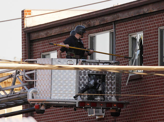 Police break out a window of an apartment where the suspect in a shooting at a movie theatre lived in Aurora, Colo., Friday, July 20, 2012. As many as 12 people were killed and 50 injured at a shooting at the Century 16 movie theatre early Friday during the showing of the latest Batman movie. (AP Photo/Ed Andrieski)