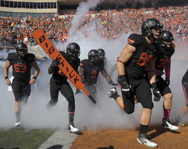 Oklahoma State players take the field at the start of an NCAA college football game against TCU in Stillwater, Okla., Oct. 27, 2012. (AP Photo/Brody Schmidt)