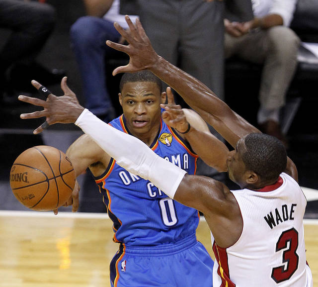 Oklahoma City Thunder point guard Russell Westbrook (0) passes against Miami Heat shooting guard Dwyane Wade (3) during the second half at Game 3 of the NBA Finals basketball series, Sunday, June 17, 2012, in Miami. (AP Photo/Wilfredo Lee) ORG XMIT: NBA137
