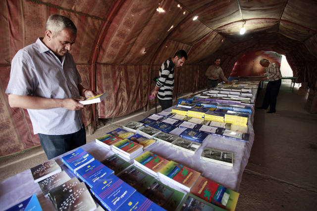 In this Monday, May 7, 2012 photo, visitors look for books at the book fair during Babylon Festival of Culture in Hillah, about 60 miles (95 kilometers) south of Baghdad. Poetry has returned to the Triangle of Death. But dancing and singing are being left out of the celebration of culture in post-Saddam Iraq. (AP Photo/Hadi Mizban)