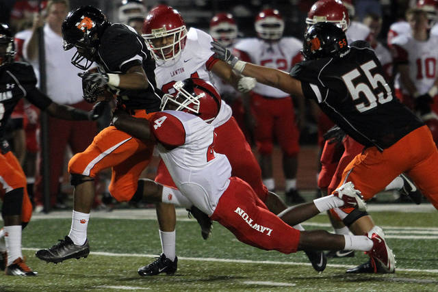 Norman running back Imond Robinson is tackled by Lawton&#039;s Curtez Zachary during the Lawton - Norman High School football game at Harve Collins Field at Norman High School in Norman Friday night. PHOTO BY HUGH SCOTT FOR THE OKLAHOMAN ORG XMIT: KOD
