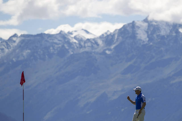 Richie Ramsay of Scotland holds a ball at the 7th hole during the fourth round of the Omega European Masters Golf Tournament in Crans Montana, Switzerland, Sunday, Sept. 2, 2012. (AP Photo/Keystone, Peter Klaunzer)