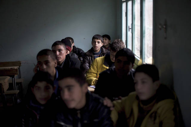 A Syrian child listens to a lecture in a classroom in a city under control of the Free Syrian Army in Aleppo province, Syria, Thursday, Dec. 13, 2012 (AP Photo/Manu Brabo) ORG XMIT: CAI115