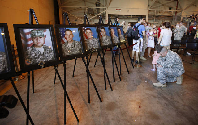 A soldier kneels in front of portraits of those who lost their lives while serving after a homecoming ceremony for about 180 Oklahoma National Guard soldiers with the 180th Cavalry Squadron returning from Kuwait and soldiers with the Oklahoma National Guard's 45th Infantry Brigade Combat Team returning from Afghanistan at the Will Rogers Air National Guard Base in Oklahoma City, Saturday, March 31, 2012. Photo by Bryan Terry, The Oklahoman