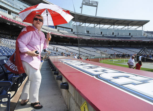 Evelyn Scalise of New York wears a Stony Brook cape and shields herself with an umbrella as she follows her nephew, Stony Brook catcher Pat Cantwell, during baseball practice at TD Ameritrade Park in Omaha, Neb., Thursday, June 14, 2012. Stony Brook will play against UCLA on Friday in the opening game of the NCAA baseball College World Series. (AP Photo/Dave Weaver)